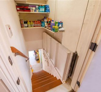 Pantry with pull-up trap door in open position, which leads to the garage and the finished basement and storage areas.