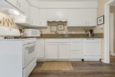Upgraded kitchen with gas stove, dishwasher, and granite counters.