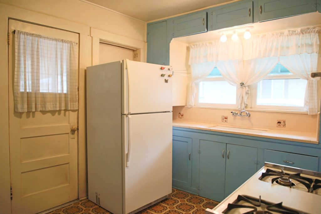 Kitchen with gas stove and doorway leading to laundry room.