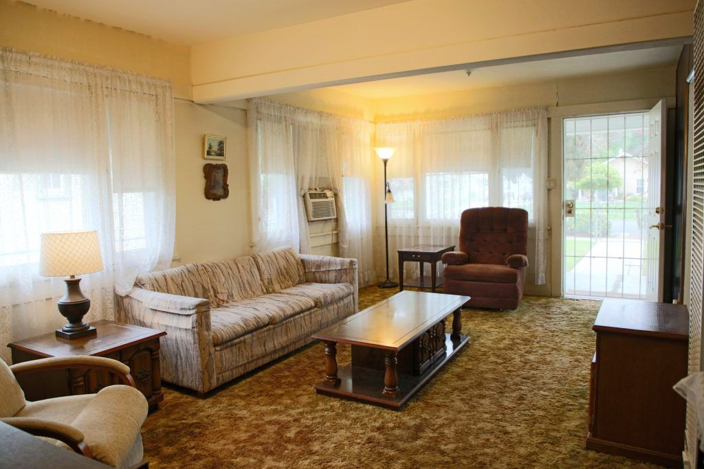 Living room with wood floors under carpeting.